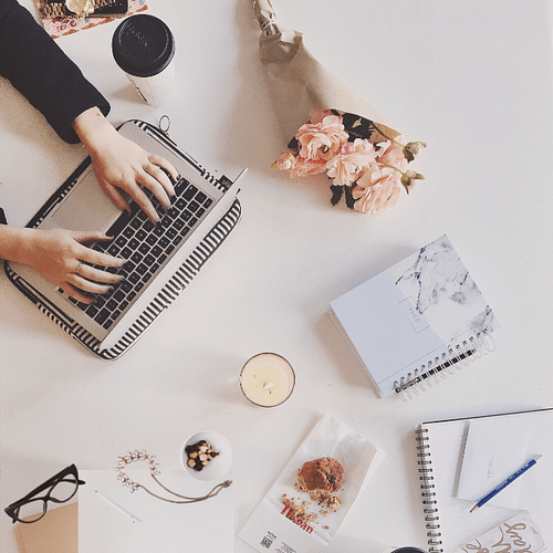 woman typing laptop flowers books candle jewelry glasses