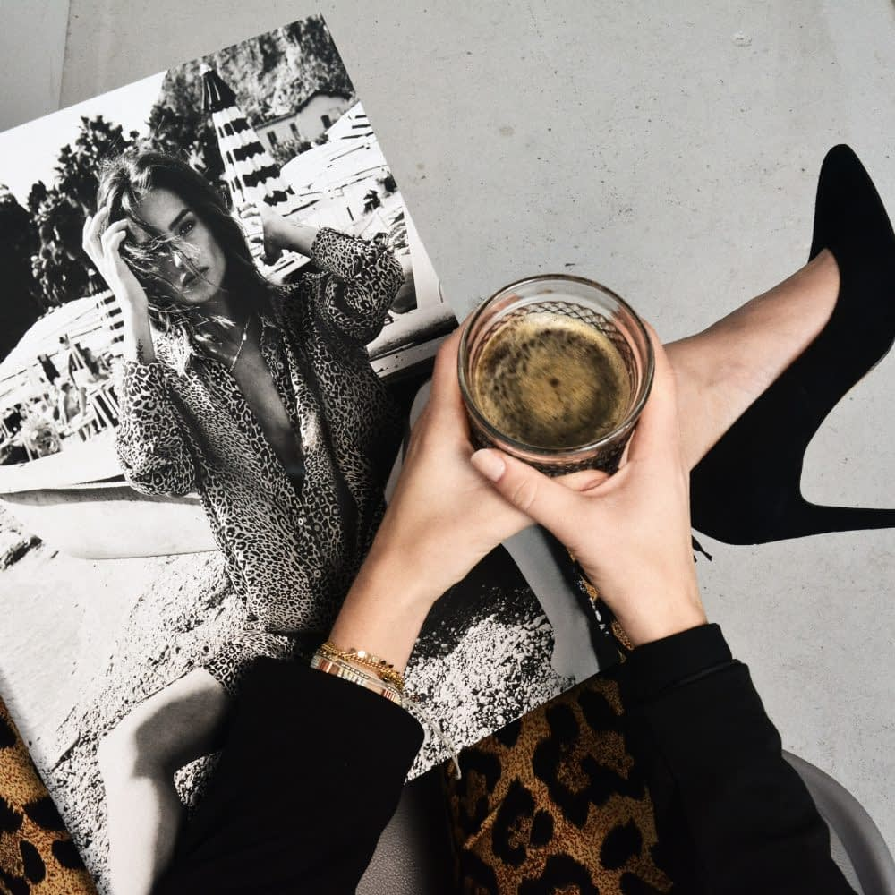 women sitting with glass and fashion book wearing black heels