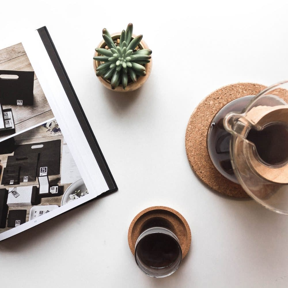 coffee cactus plant and book on white desk