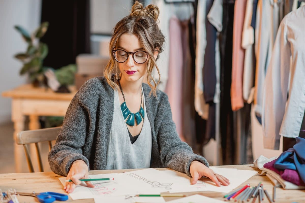fashion girl sitting at desk working with rack of clothes behind her