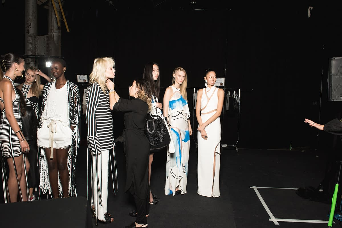 backstage fashion show models lined up stylist fixing model while lined up